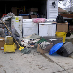 Soaked, wet personal items sitting in a driveway, including a washer and dryer in Smiths Falls.